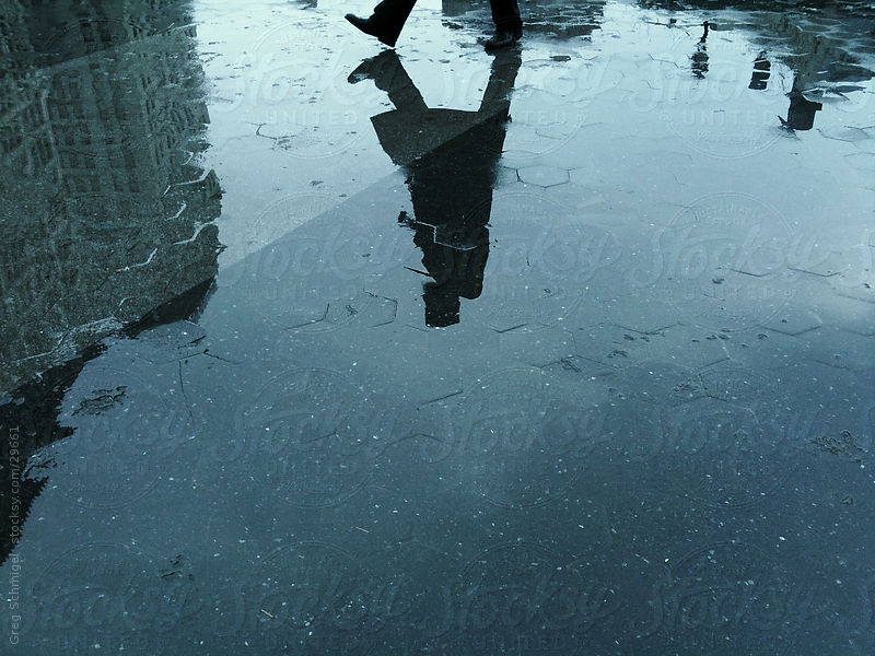 Man walking in rain reflection